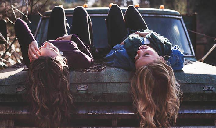 Najlepšie kamarátky sediace na kapote auta