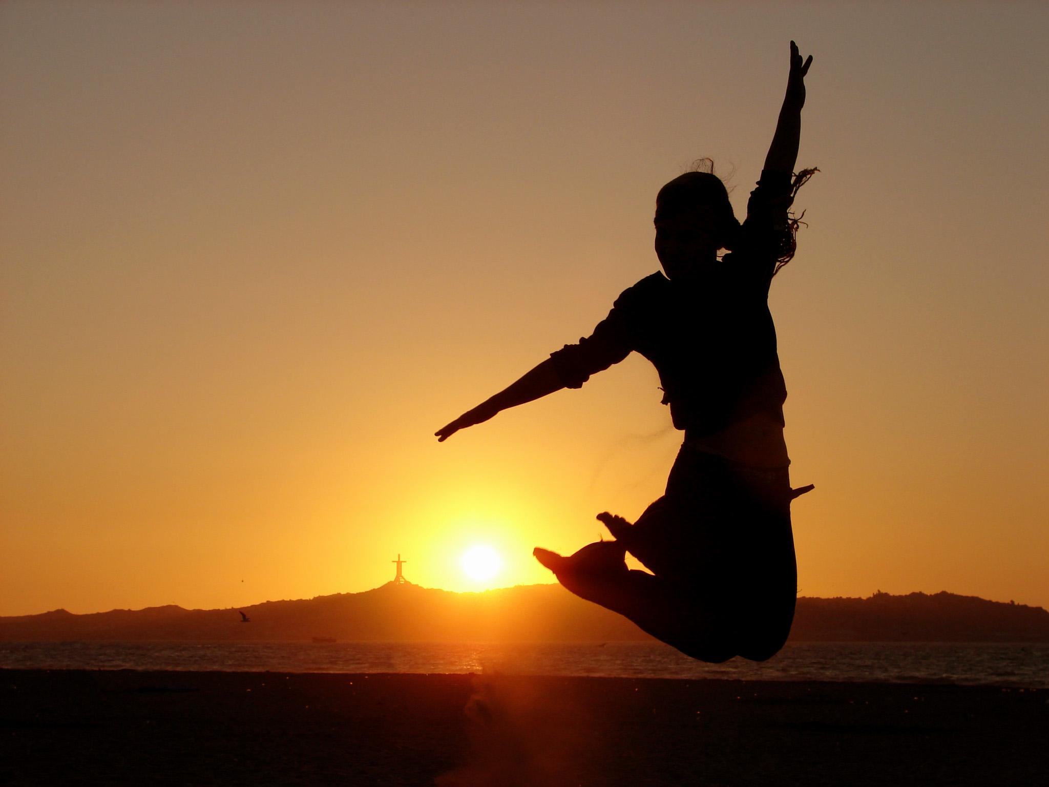 šťastný výskok pri západe slnka