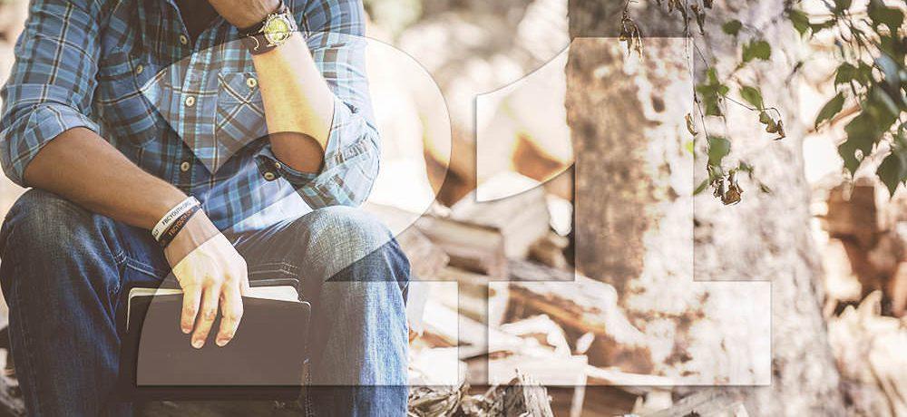 Muž sediaci v lese čítajúci knihu