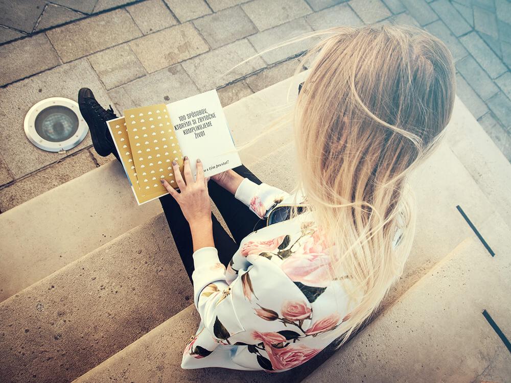 Dievča si číta knihu 100 Spôsobov, Ktorými Si Zbytočne Komplikujeme Život (a ako s tým prestať!) od Dušana Kadleca - Motivation-Man.sk