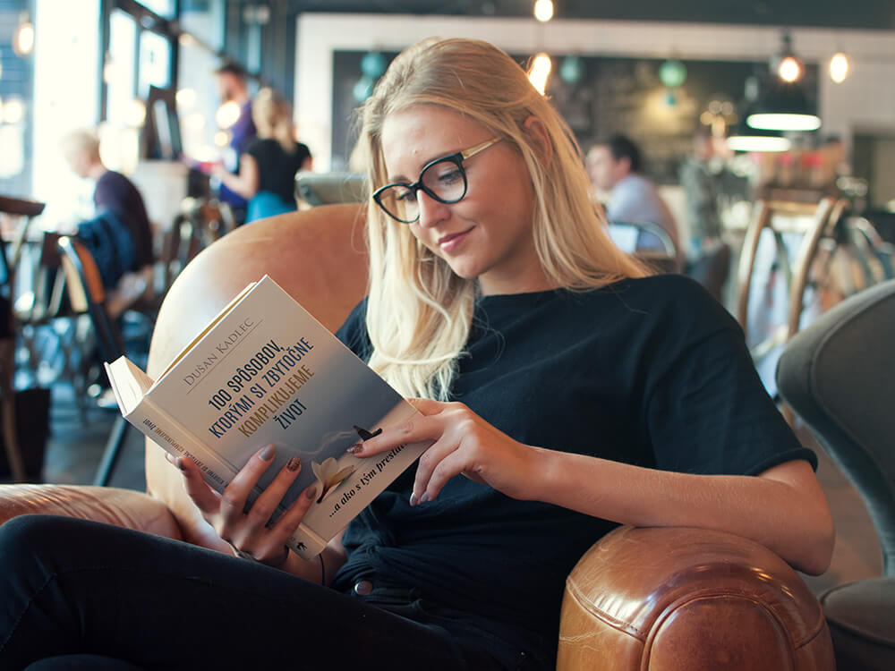 Dievča si číta knihu 100 Spôsobov, Ktorými Si Zbytočne Komplikujeme Život (a ako s tým prestať!) od Dušana Kadleca